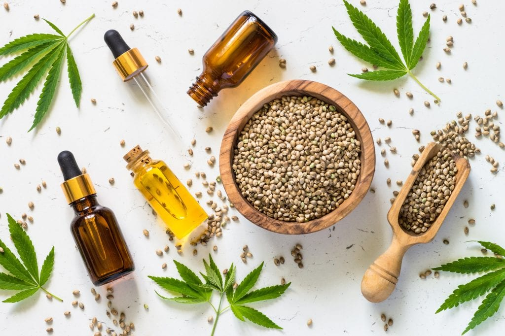 Cannabis oil and cannabis seeds at white